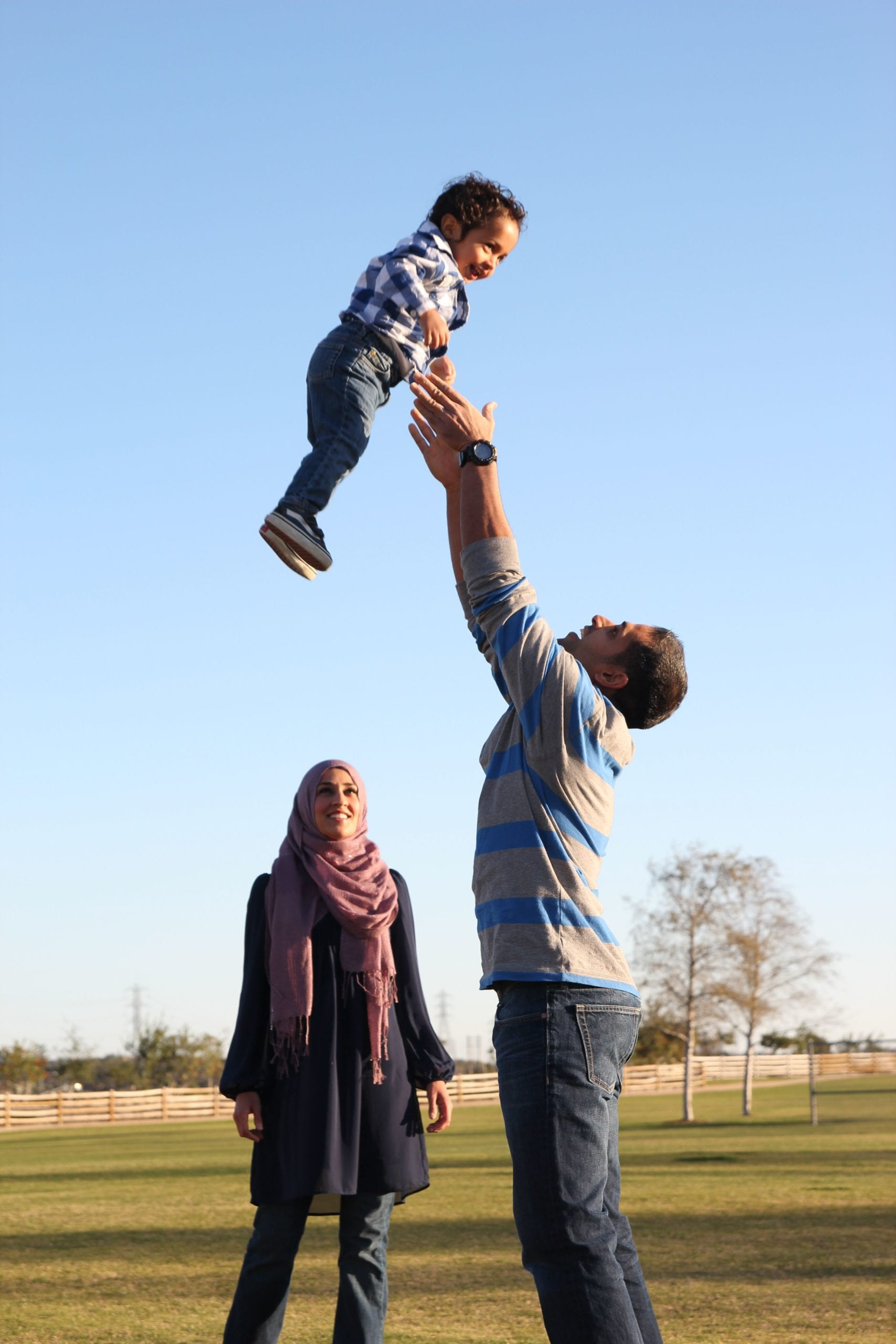 man throwing his child in the air