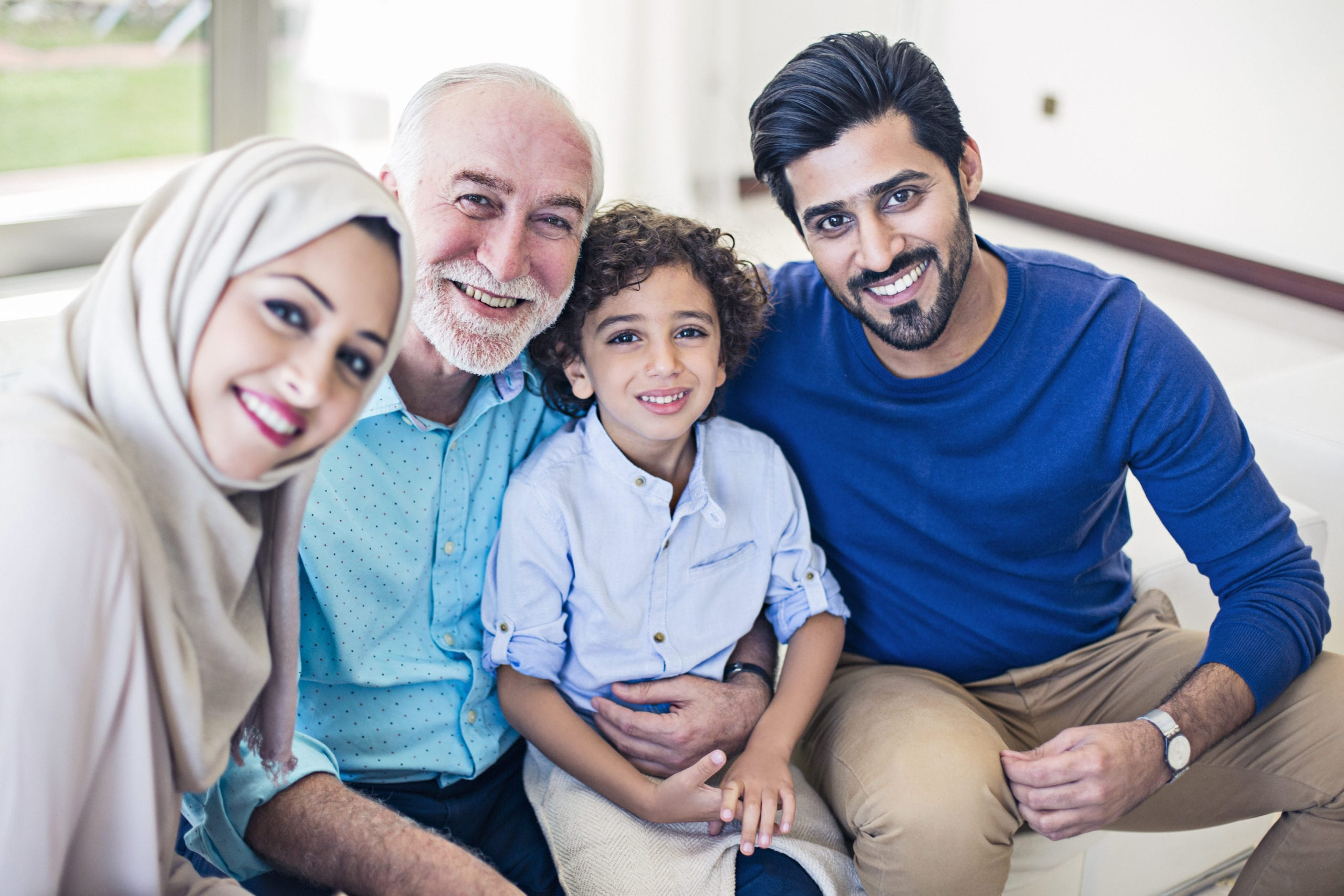 Muslim family portrait, kid, parents and grandfather all looking at the camera.