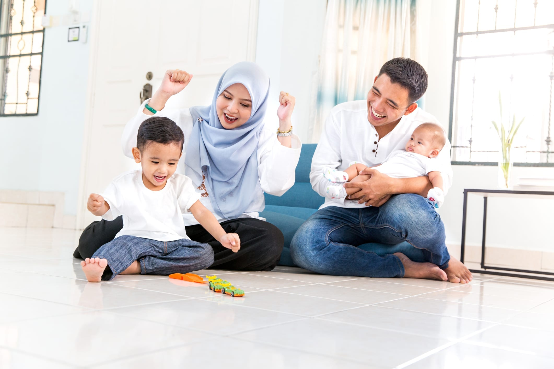 family cheering child playing with toys