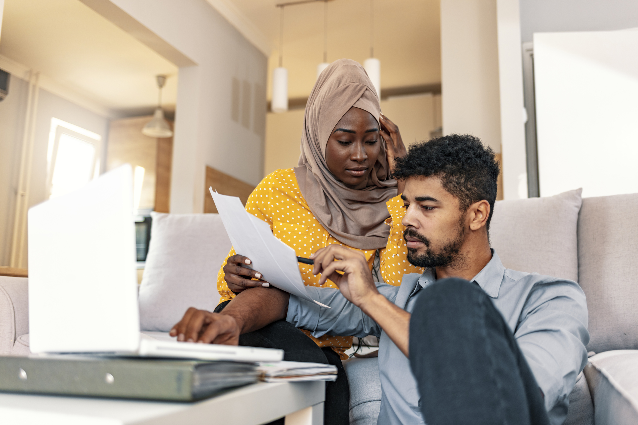 Young muslim African family of two managing finances at home, reviewing bank accounts, sitting with notebook computer. Wife and husband paying taxes online on laptop.